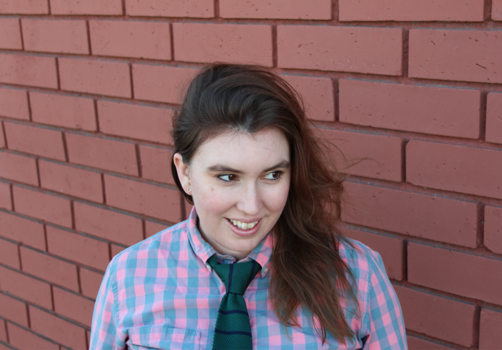headshot of LJ Pemberton, a white woman with long brown hair smiling and wearing a checked shirt and silk tie